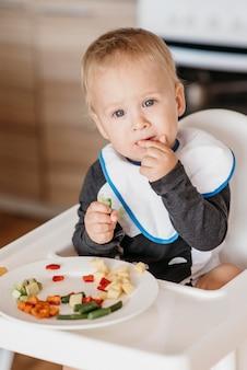 Bebê fofo na cadeira alta comendo