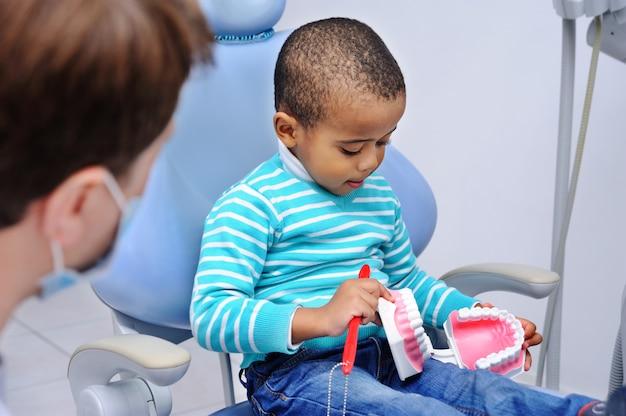 Bebê fofo na cadeira odontológica