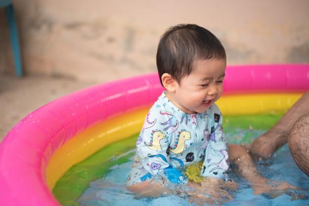 Bebê fofo nadando na pequena piscina