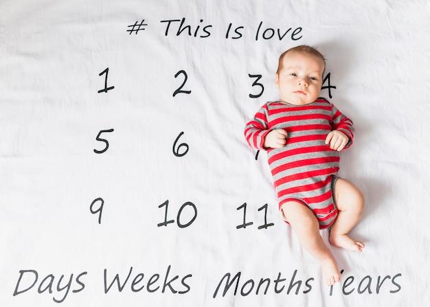 Bebê fofo no corpo listrado com calendário