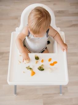 Bebé fofo numa cadeira alta a comer vegetais sozinho