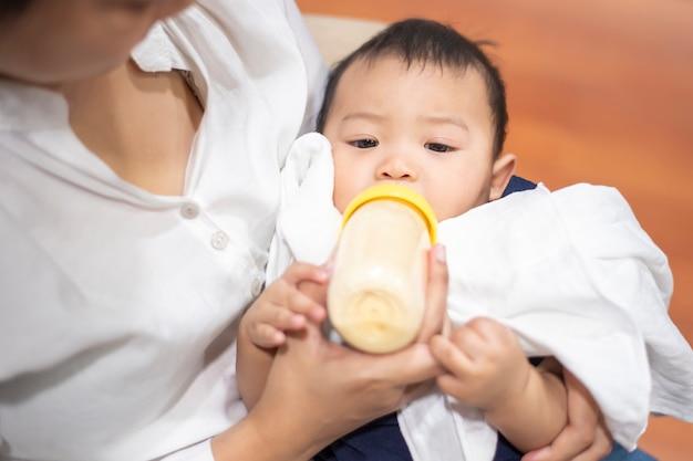 Bebê fofo recém-nascido está bebendo leite da garrafa pela mãe