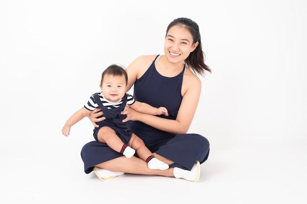 Bebê fofo recém-nascido feliz e linda mãe em estúdio