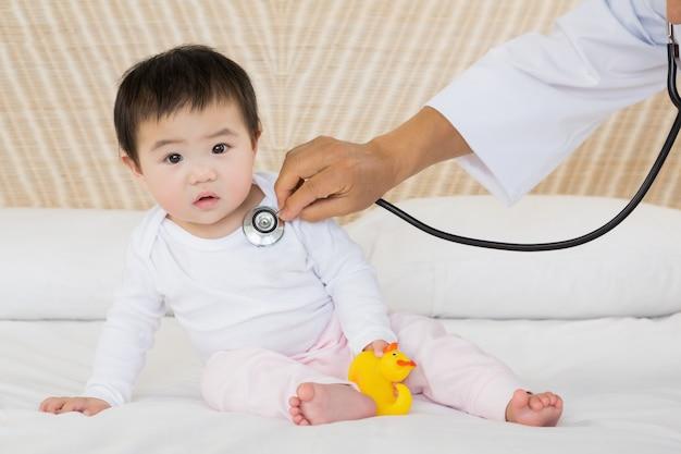 Bebê fofo sendo visitado pelo médico na cama