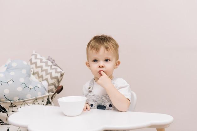 Bebê fofo sentado à mesa e comer nas cores brilhantes do quarto infantil.