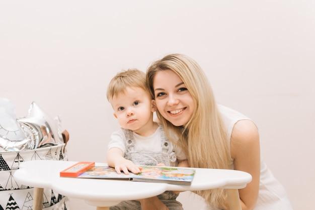 Bebê fofo sentado à mesa e lendo um livro com sua mãe nas cores brilhantes do berçário.