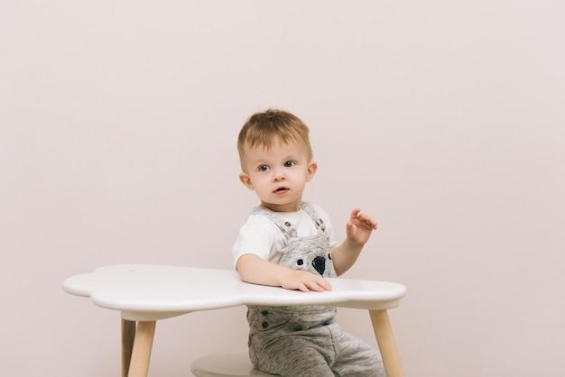 Bebê fofo sentado à mesa