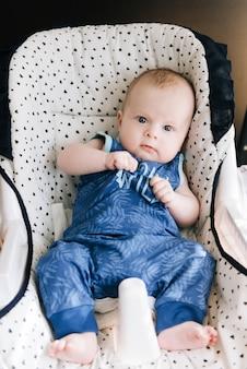 Bebê fofo sentado em uma cadeira alta, balanços