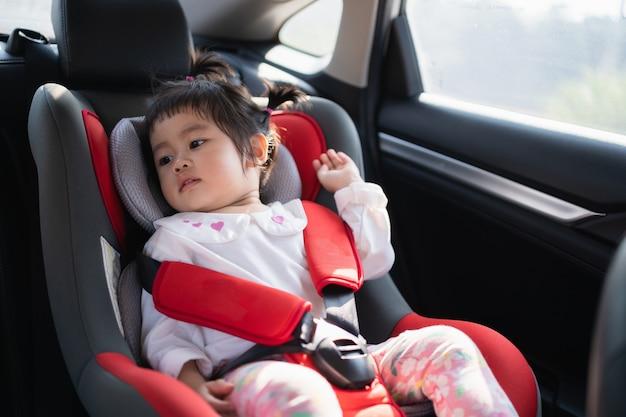 Bebê fofo sentado em uma cadeira de segurança