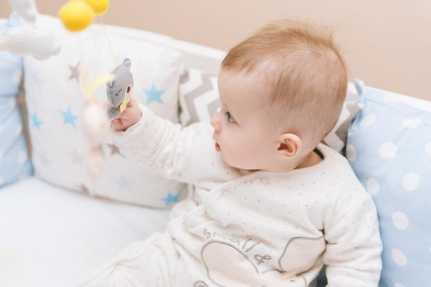 Bebê fofo sentado em uma cama redonda branca. creche leve para crianças pequenas. brinquedos para berço infantil. criança sorridente, brincando com móveis de feltro no quarto ensolarado.