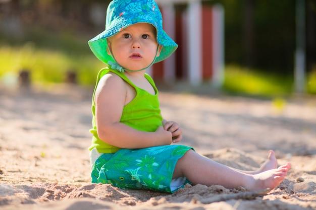 Bebê fofo sentado na areia