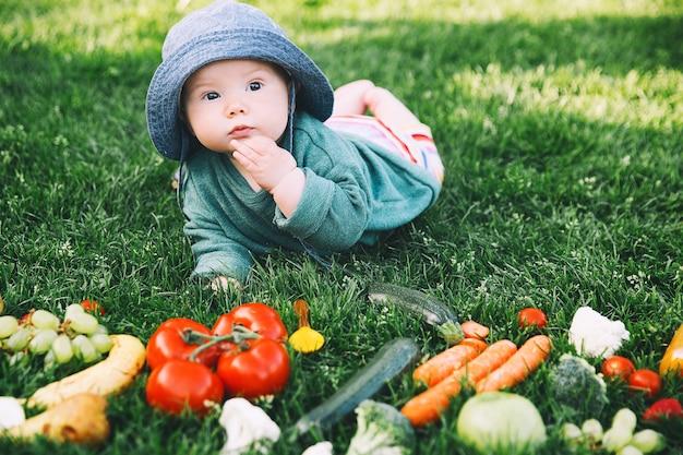 Bebê fofo sorridente e diferentes frutas e vegetais frescos na grama verde