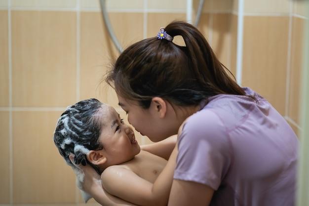 Bebê fofo tomando banho com a mãe no banheiro