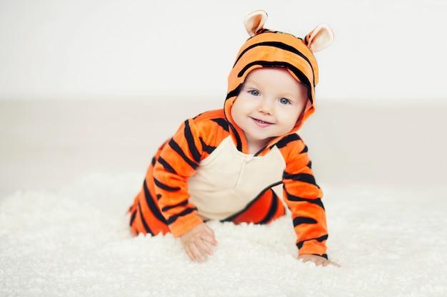 Bebê fofo vestido com um tigre brilhante