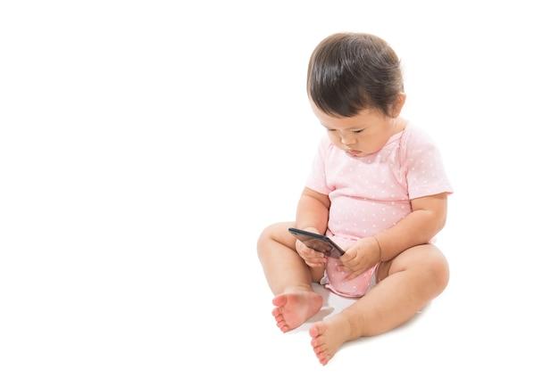 Bebé infantil da criança que joga o telefone móvel isolado em um fundo branco