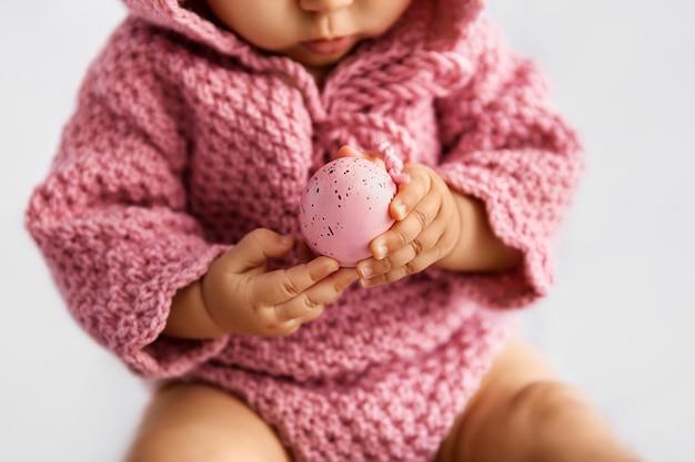 Bebê infantil de rosa, segurando o ovo de páscoa nas mãos, foco seletivo