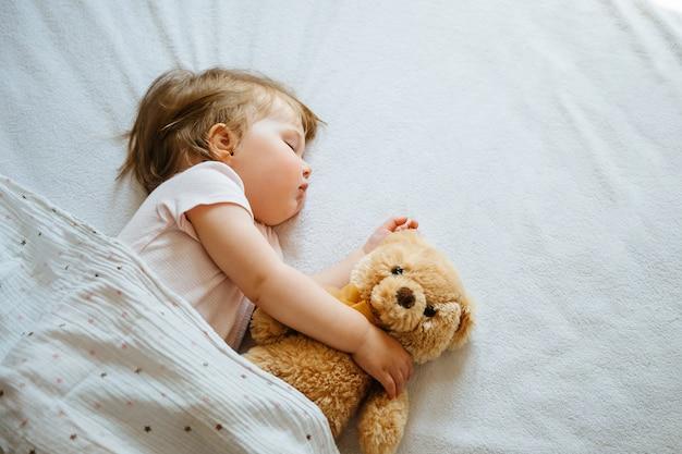 Bebê infantil dormindo nas folhas brancas, abraçando o brinquedo macio, espaço livre.