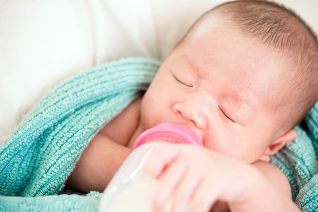 Bebê inocente recém-nascido dormindo bebendo leite da mamadeira