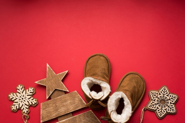 Bebê inverno natal vermelho com botas, árvore de madeira e flocos de neve. feriado criança
