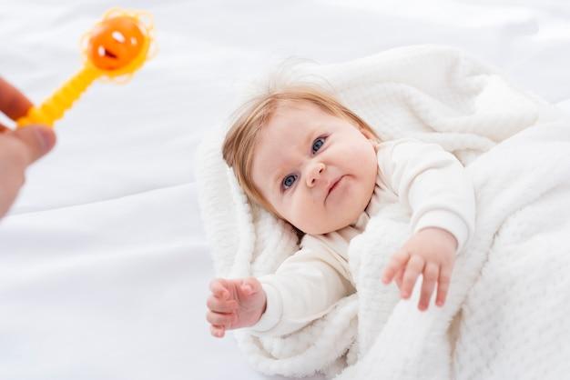 Bebê irritado em cobertor querendo brinquedo