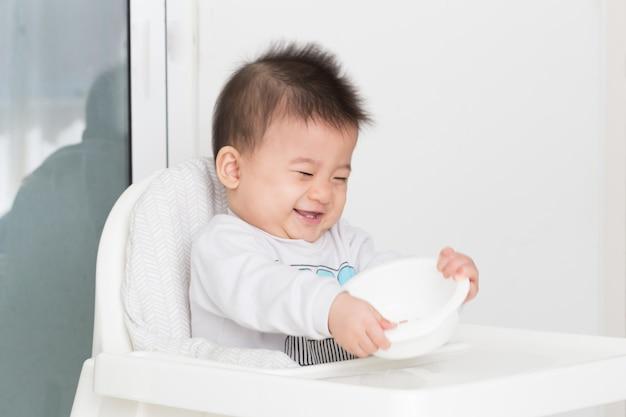 Bebê jogando tigela de plástico enquanto aguarda o café da manhã