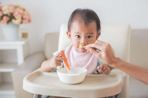 Bebê jovem feliz na cadeira alta sendo alimentada