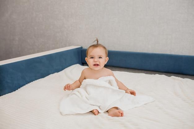 Bebê linda menina sentada no sofá em uma toalha