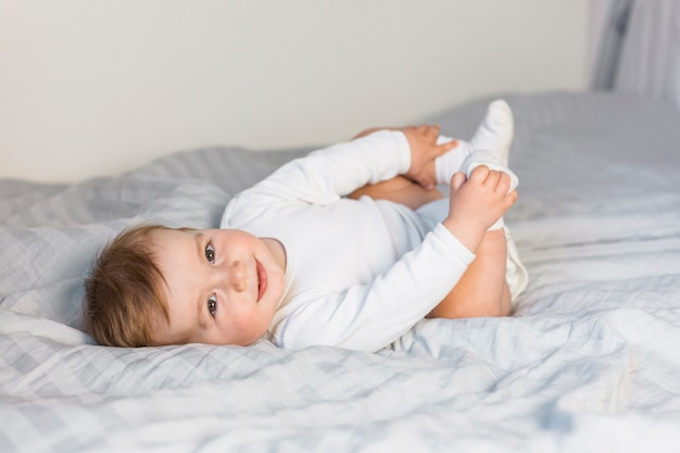 Bebê loiro bonito na cama branca, brincando com os pés