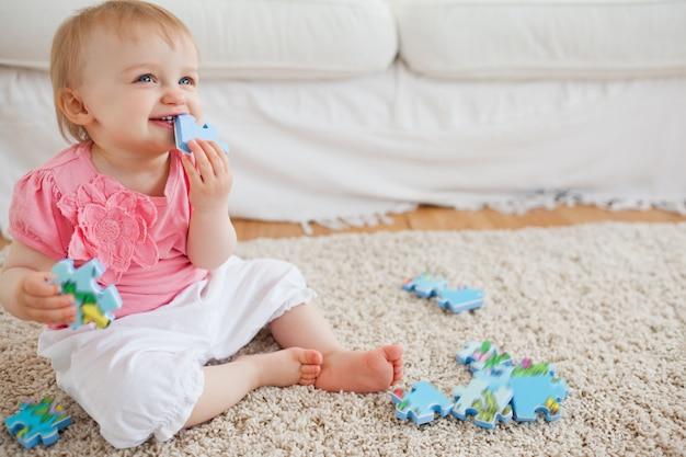 Bebê loiro brincando com peças de quebra-cabeça enquanto está sentado em um tapete