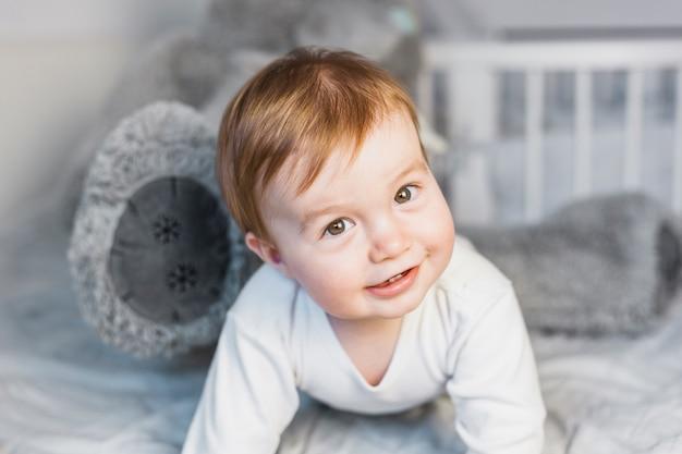 Bebê loiro fofo na cama branca com ursinho de pelúcia