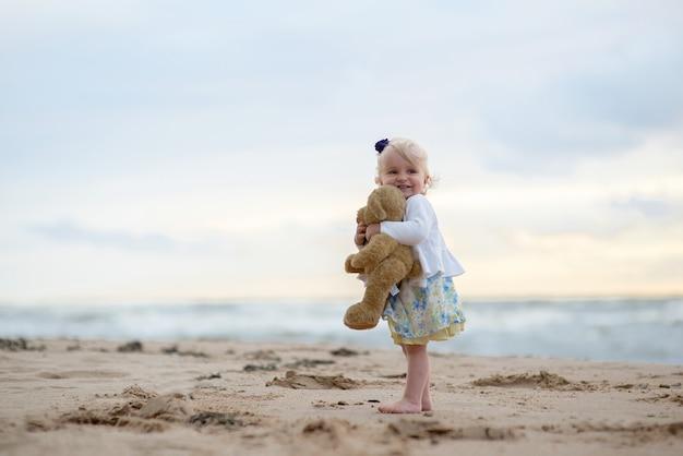 Bebê menina bonitinha com ursinho de pelúcia na praia