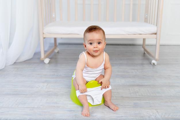 Bebê menina bonitinha sentada em um penico