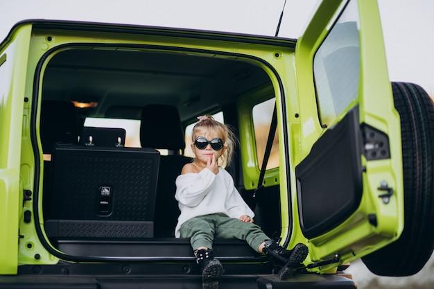 Bebê menina bonitinha sentada na parte traseira sente-se do carro