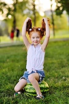 Bebê menina engraçada com cabelo vermelho, apoiando-se em uma enorme melancia no parque na grama