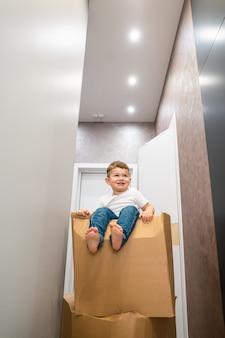 Bebê menino bonitinho sentado na caixa de papelão