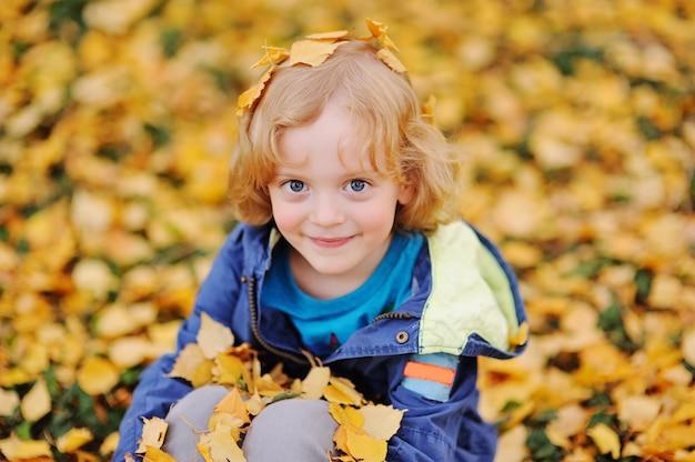 Bebê - menino com cabelo loiro encaracolado sorrindo contra folhas de outono amarelas no parque