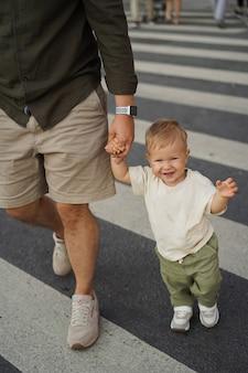 Bebê menino cruzando a estrada na passadeira segurando o pai com a mão na cidade de são petersburgo, rússia Foto Premium
