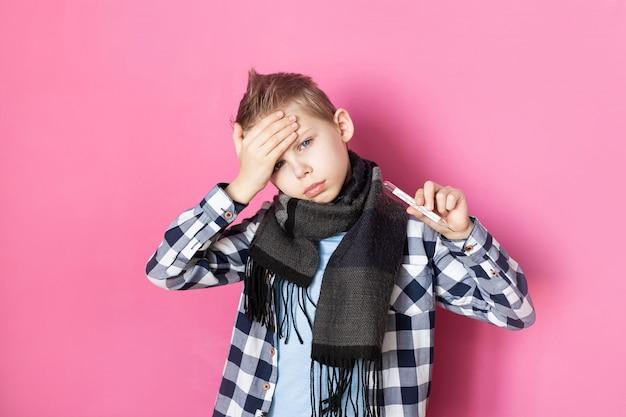 Bebê, menino de 8 a 9 anos de idade na parede rosa doente, segura um termômetro