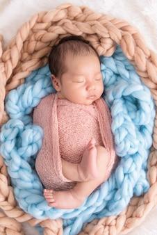 Bebê menino dormir em um pano branco wrap feelgood relaxante