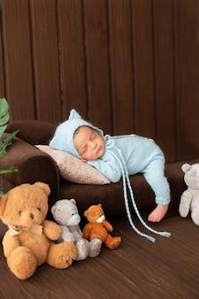 Bebê menino recém-nascido descansando no sofá marrom em pijama de malha azul, rodeado por ursos de brinquedo bonito