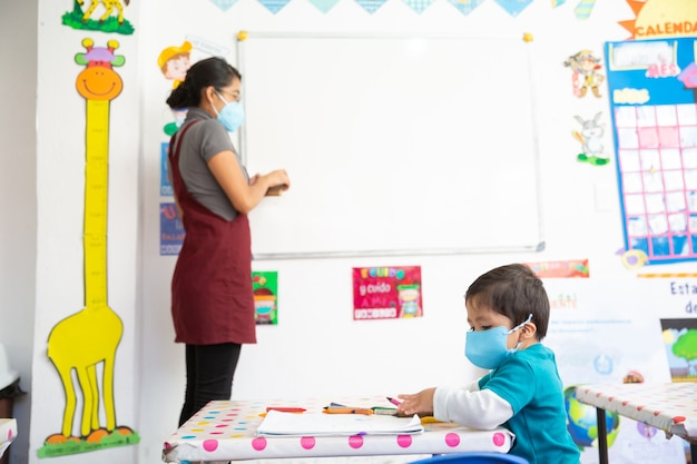 Bebê mexicano com máscara facial tendo aulas na escola e professora ao fundo