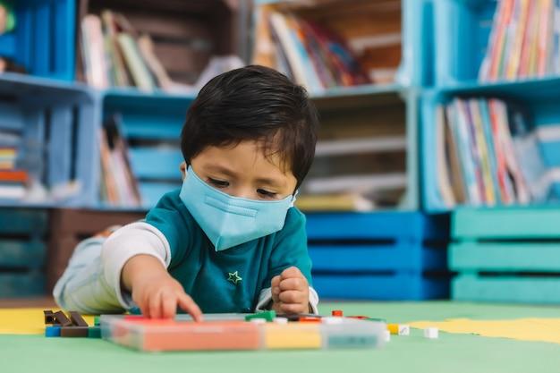Bebê mexicano na escola com máscara brincando com peças coloridas em um tapete