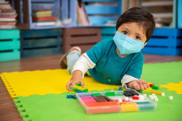 Bebê mexicano na escola com máscara brincando com peças coloridas no tapete olhando para a câmera