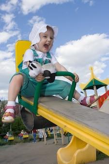 Bebê muito feliz balançando no céu azul com nuvens