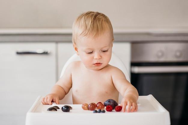 Bebé na cadeira alta a escolher que fruta comer