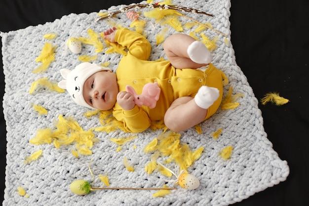 Bebê na colcha. bebê com roupas amarelas.
