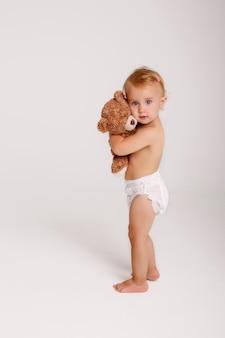 Bebé na fralda que joga com o urso de peluche no branco.