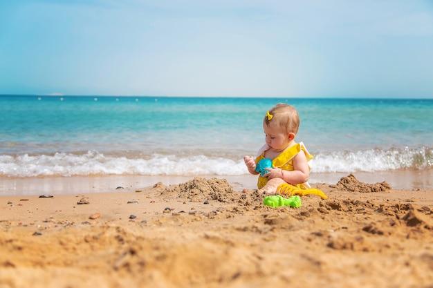 Bebê na praia perto do mar brincando com brinquedos