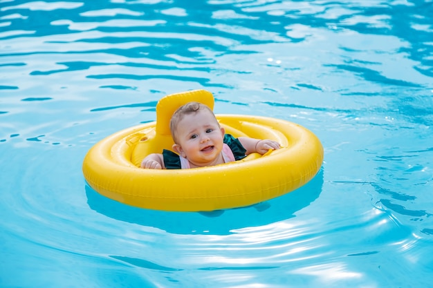 Bebê nadando em um anel de borracha no mar