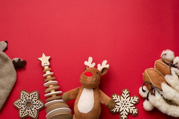 Bebê natal plano de fundo, criança inverno plana leigos decoração de madeira, veados, pano em fundo vermelho